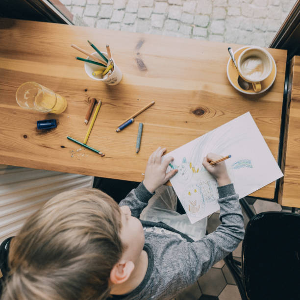Little boy drawing  in cafe stock photo