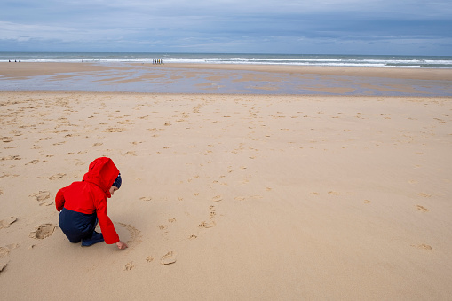 istock Little Boy drawing in the sand on the beach in cold windy weather 1174811270
