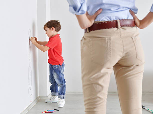 Little Boy Drawing On Wall With Crayons Stock Photo