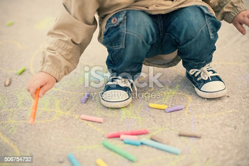istock Little boy drawing with sidewalk chalks 506754732