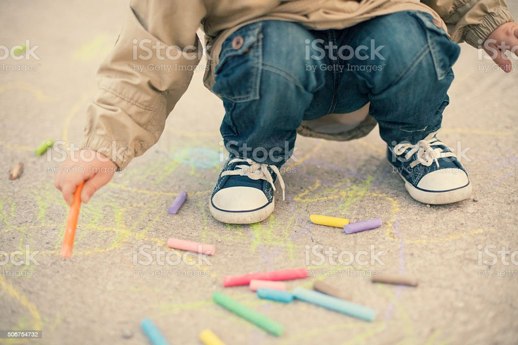 Little boy drawing with sidewalk chalks stock photo