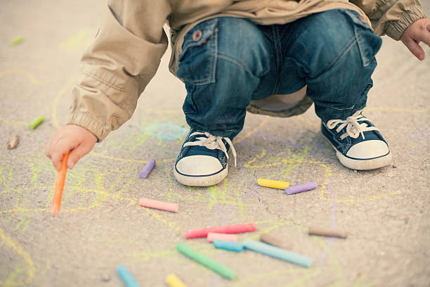 little boy drawing with sidewalk chalks - chalk drawing stock photos and pictures