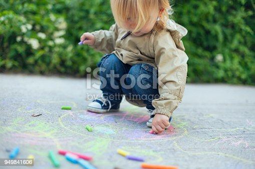 istock Little boy drawing with sidewalk chalks 949841606