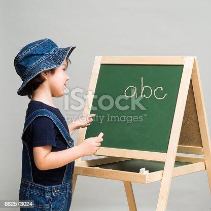 istock Little boy draws chalk on a school board 662573024