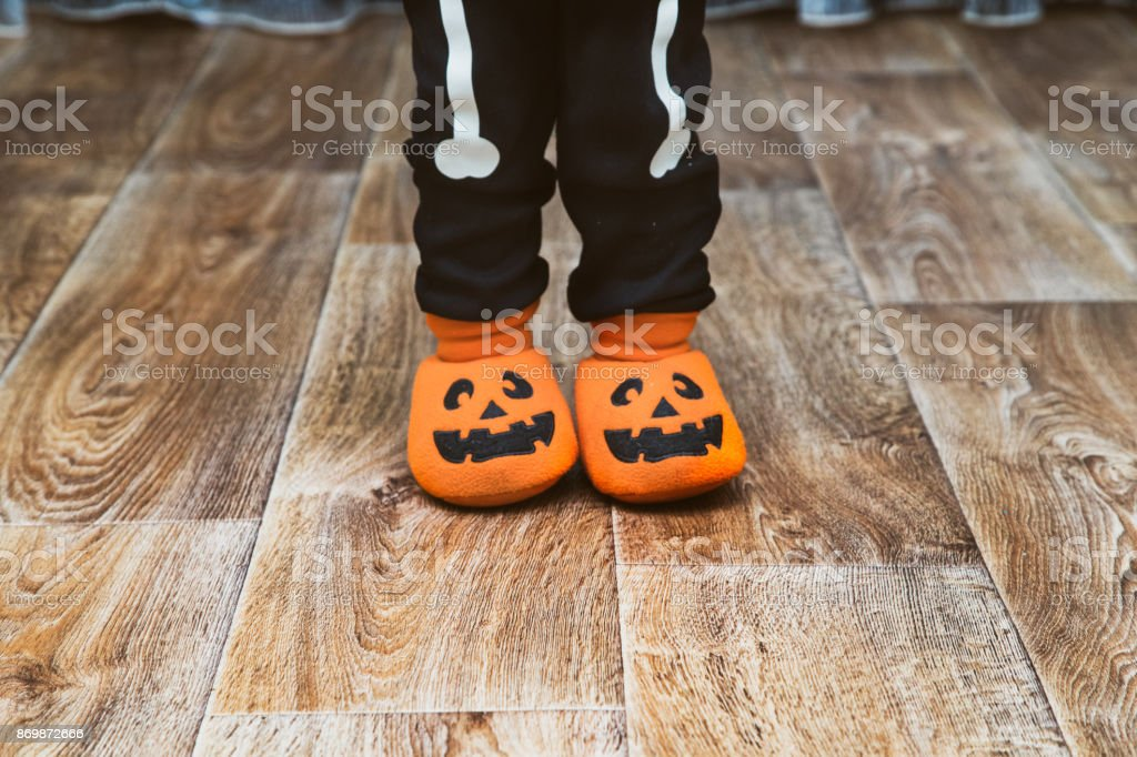 Little boy dressed in skeleton costume and pumpkin slippers is standing in center of room stock photo