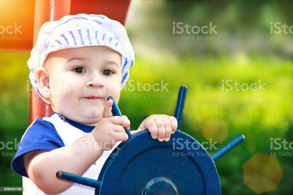 Little boy dressed up as a sailor holding the steering wheel stock photo