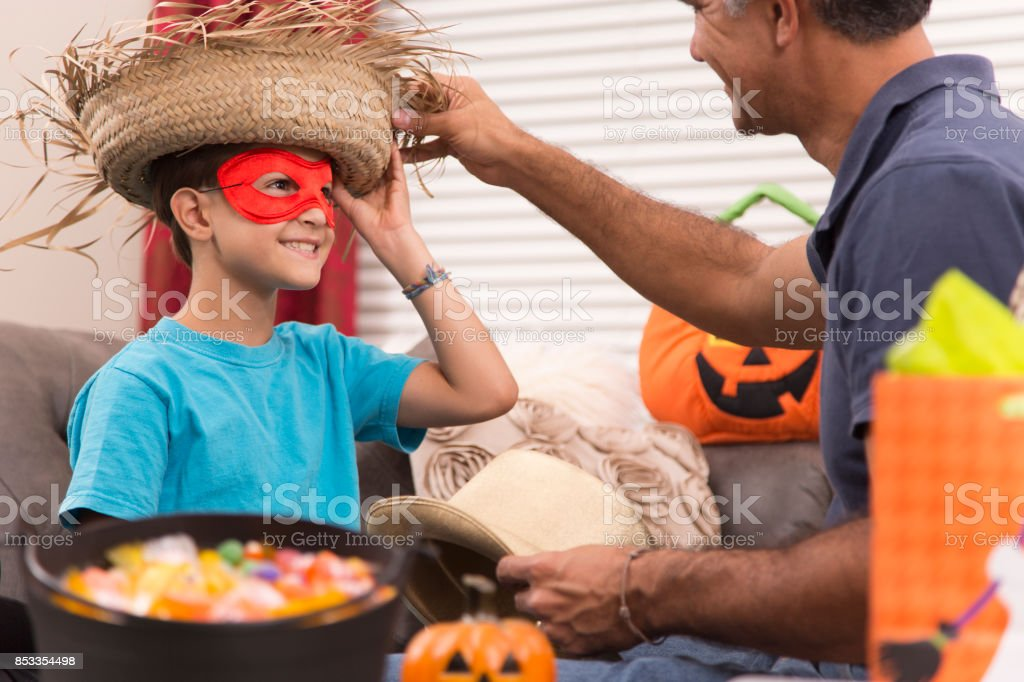 Little boy dresses up for Halloween with dad's help. stock photo