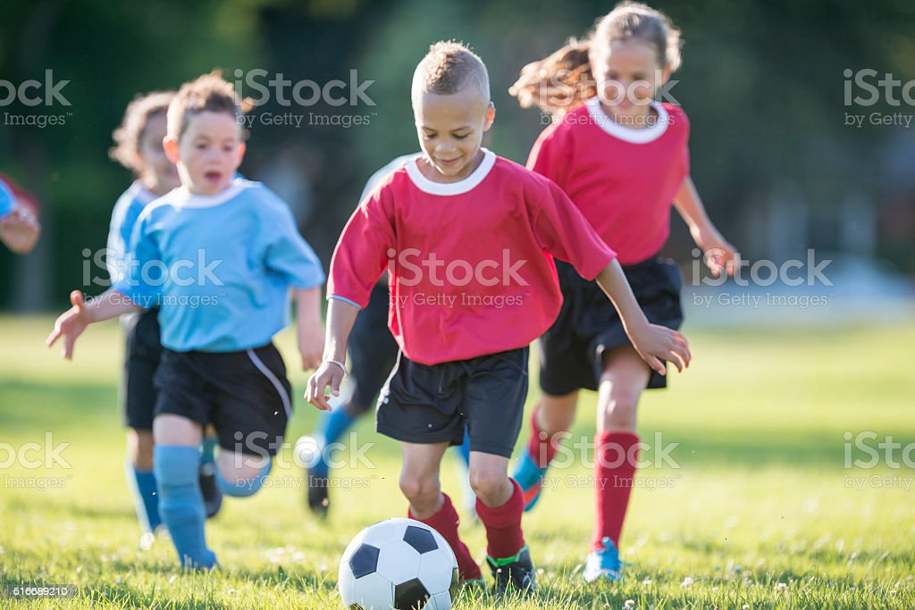 Little Boy Dribbling the Ball Up the Field stock photo