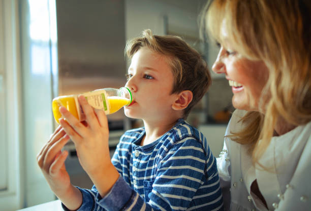 little  boy drinking fresh orange juice. - drinking juice stock photos and pictures