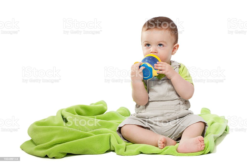 Little boy drinking from baby cup stock photo