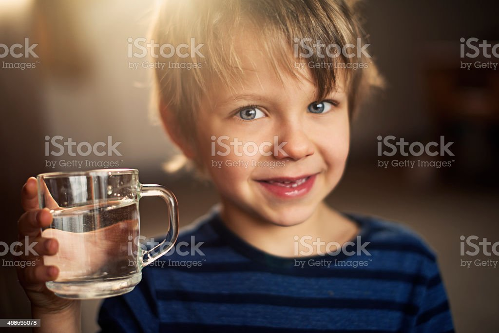 Little boy drinking glass of water. stock photo