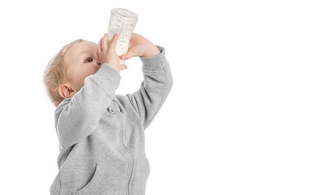 Little boy drinking milk from bottle stock photo