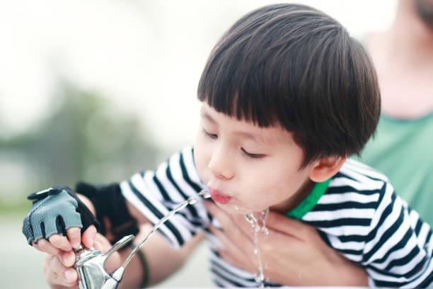 Little boy drinking tap water stock photo