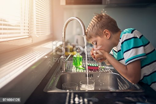 Little boy drinking tap water. Little boy aged 8 is drinking tap water in kitchen