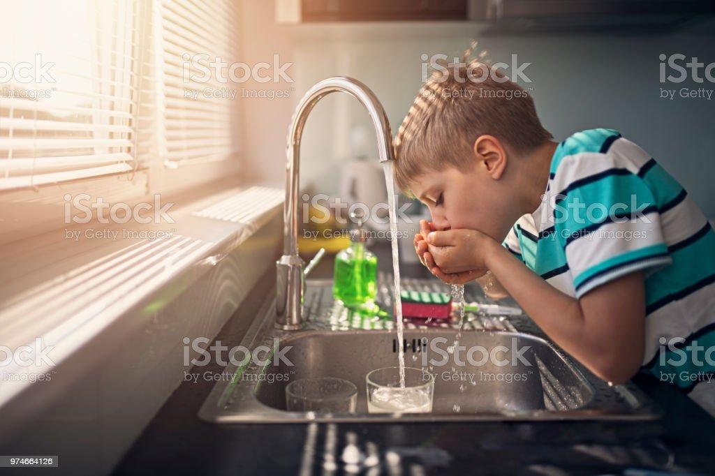 Kleine Junge trinkt Leitungswasser – Foto