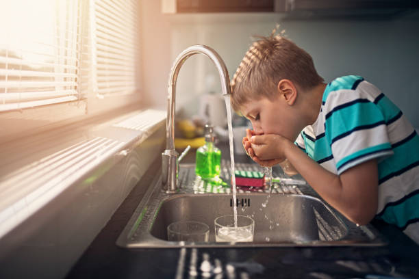 little boy drinking tap water - drinking water stock photos and pictures