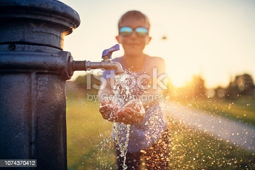 Little thirsty boy drinking water from public fountain. Nikon D850