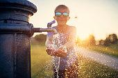 Little boy drinking water from public fountain