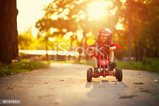 Happy little boy aged 6 is driving a go-kart (or kart, soapbox car, cyclekart). Road and sunset visible in the background. The boy is wearing a helmet and racer outfit.