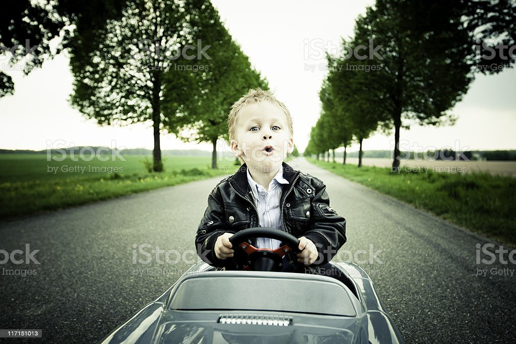 Little Boy Driving a Toy Car stock photo