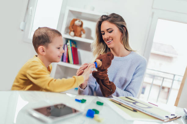 Little boy during lesson with his speech therapist. Little boy during lesson with his speech therapist. Learning through fun and play autism stock pictures, royalty-free photos & images