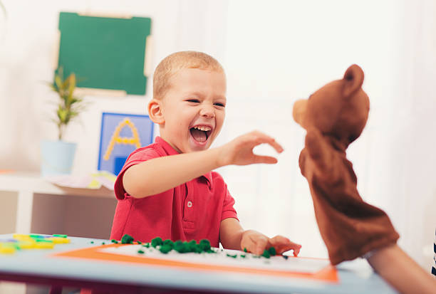 Little boy during lesson with his speech therapist. stock photo