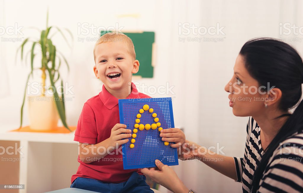 Little boy during lesson with his speech therapist stock photo