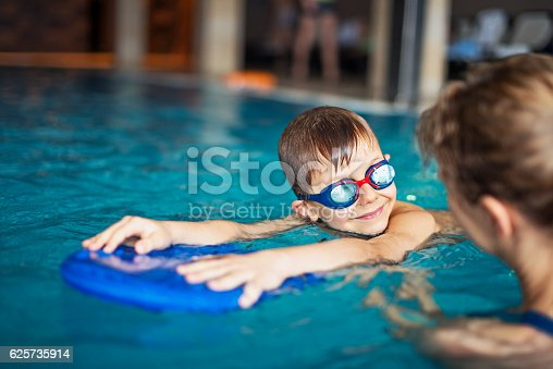 istock Little boy during swimming lesson at indoors swimming pool 625735914