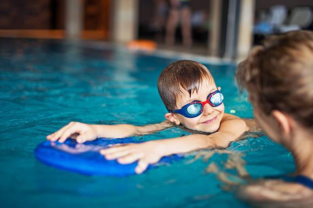 niño pequeño durante la clase de natación en la piscina cubierta - natación fotografías e imágenes de stock