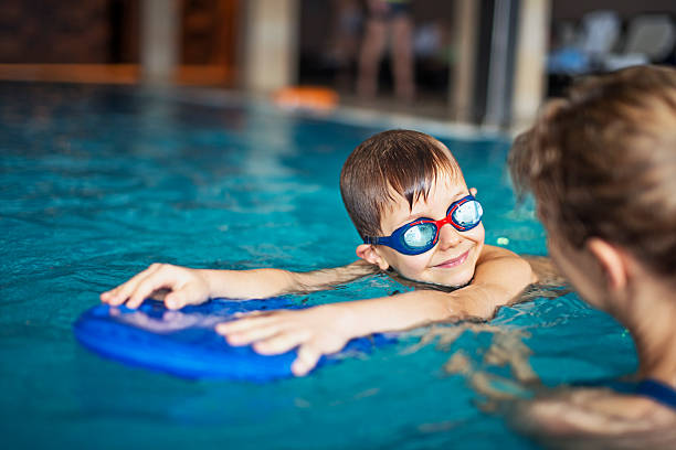 little boy during swimming lesson at indoors swimming pool - 水泳 ストックフォトと画像