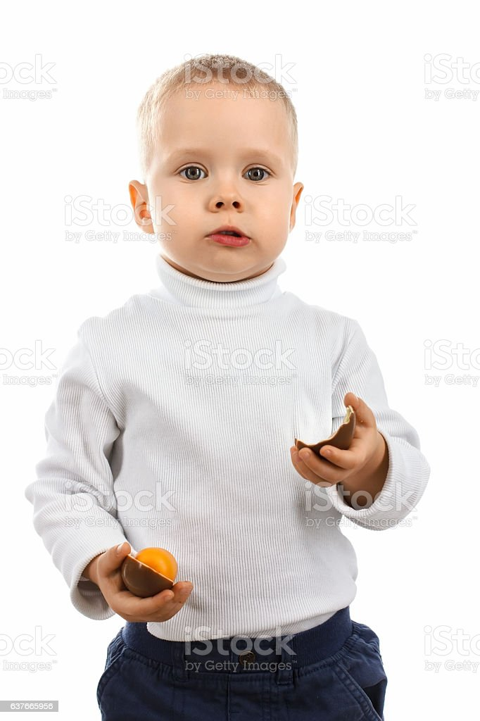 Little boy eating a delicious chocolate Easter egg stock photo