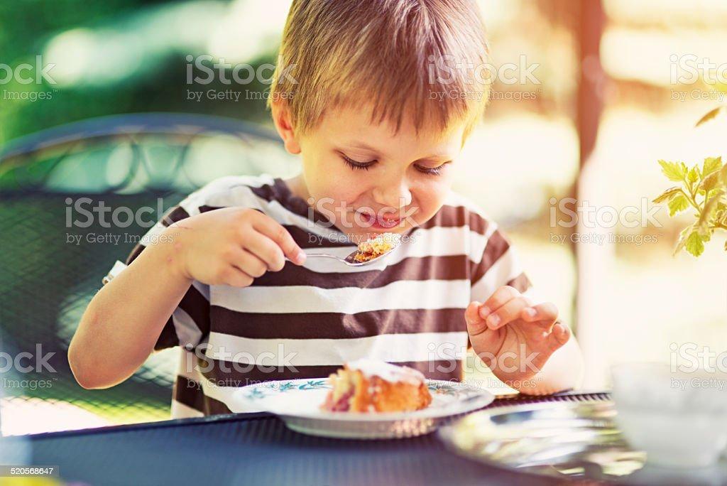 Little boy eating a delicious dessert stock photo
