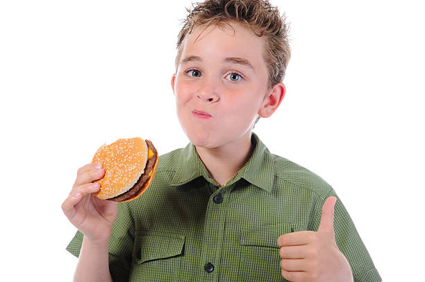 Little boy eating a hamburger stock photo