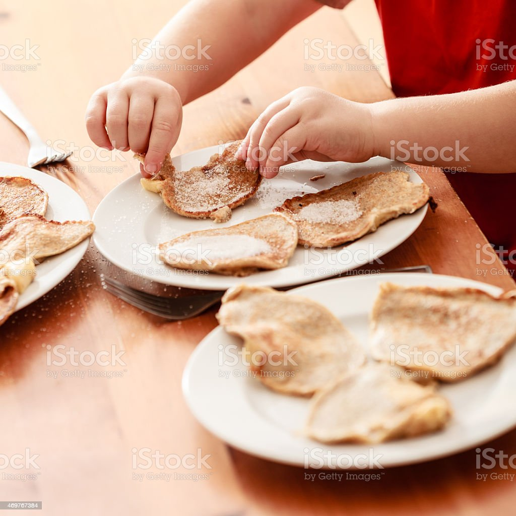 Little boy eating apple pancakes at home stock photo
