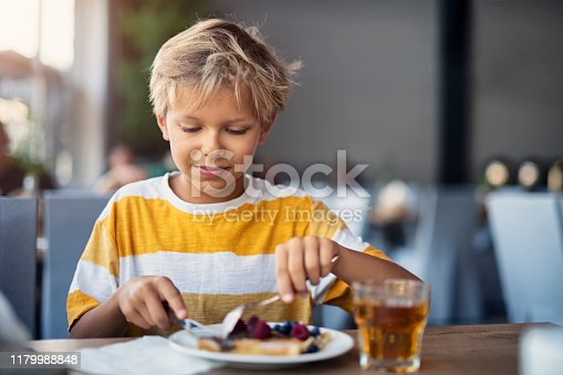 Little boy having crepes for breakfast. The crepes are sprinkled with fruits - blueberries and raspberries Nikon D850