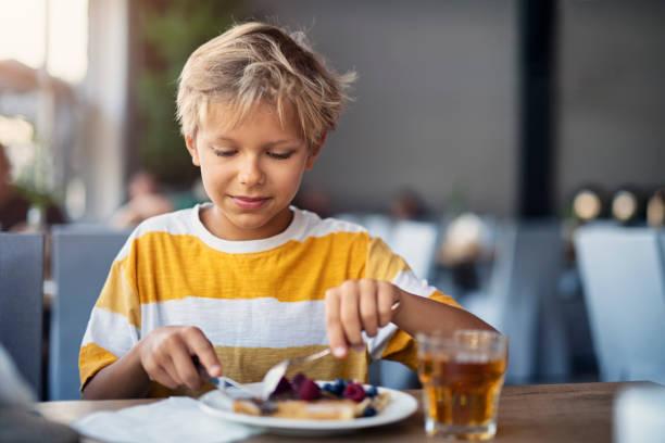 liten pojke äter frukost crepes med frukter - bordsskick bildbanksfoton och bilder