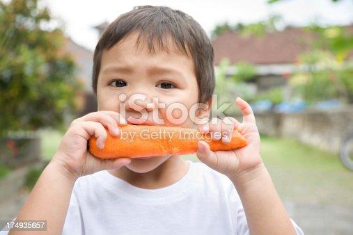 istock Little boy eating carrot 174935657