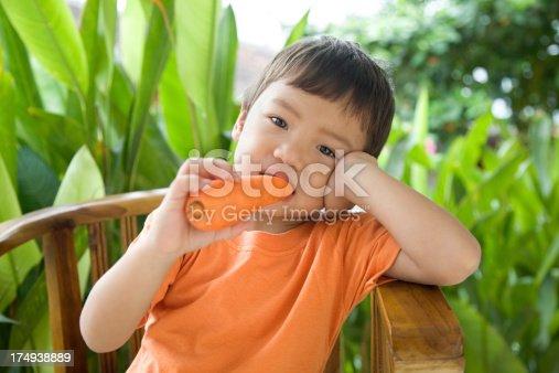 istock Little boy eating carrot 174938889