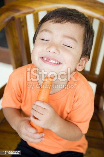 istock Little boy eating carrot 174950037