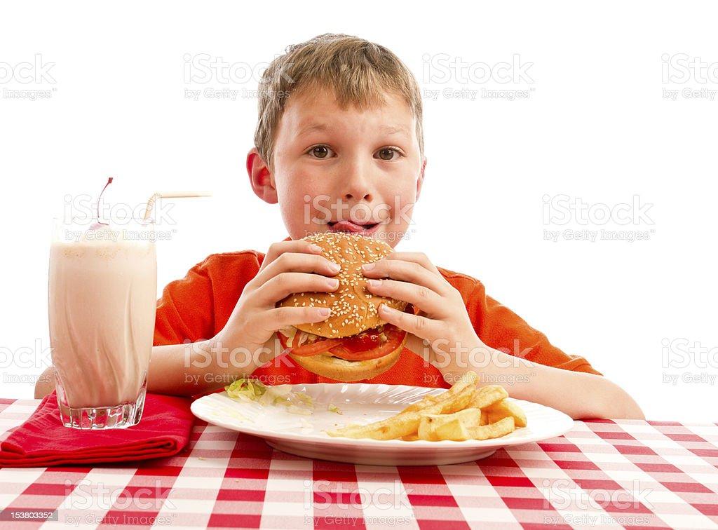 Little Boy Eating Cheeseburger, Isolated on White with Milkshake royalty-free stock photo