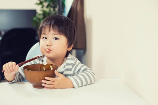 Little boy eating dinner at home stock photo