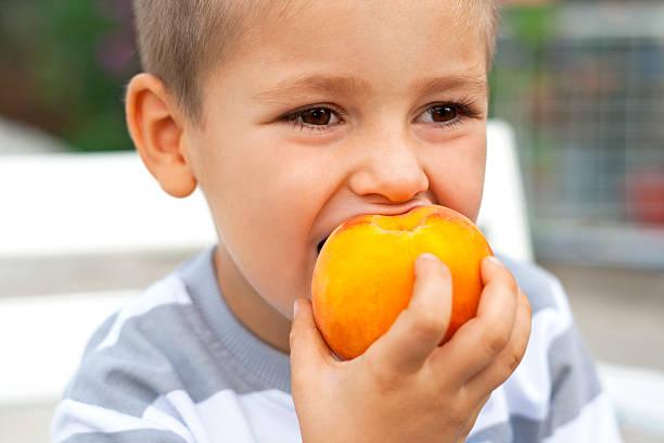 ragazzino mangiare frutta fresca - pesche bambino foto e immagini stock