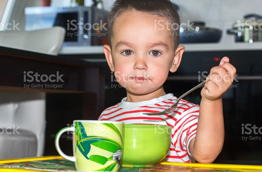 Little boy eating in kitchen royalty-free stock photo