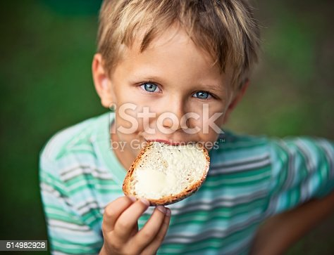 Portrait of little boy aged 5 eating loaf of bread with butter outdoors. Summer vacations.