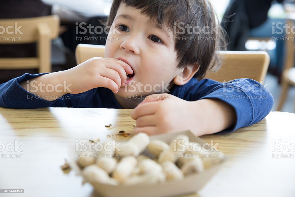 Little boy eating nuts stock photo