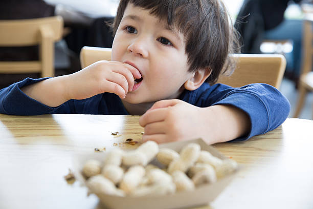 little boy eating nuts - peanut food stock photos and pictures