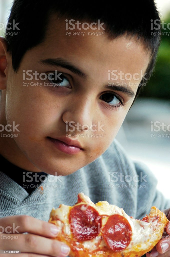 Little boy eating pepperoni pizza royalty-free stock photo