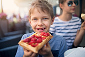 Little boy aged 8 eating waffle with strawberries. Sister eating ice cream in the background.\nNikon D850.