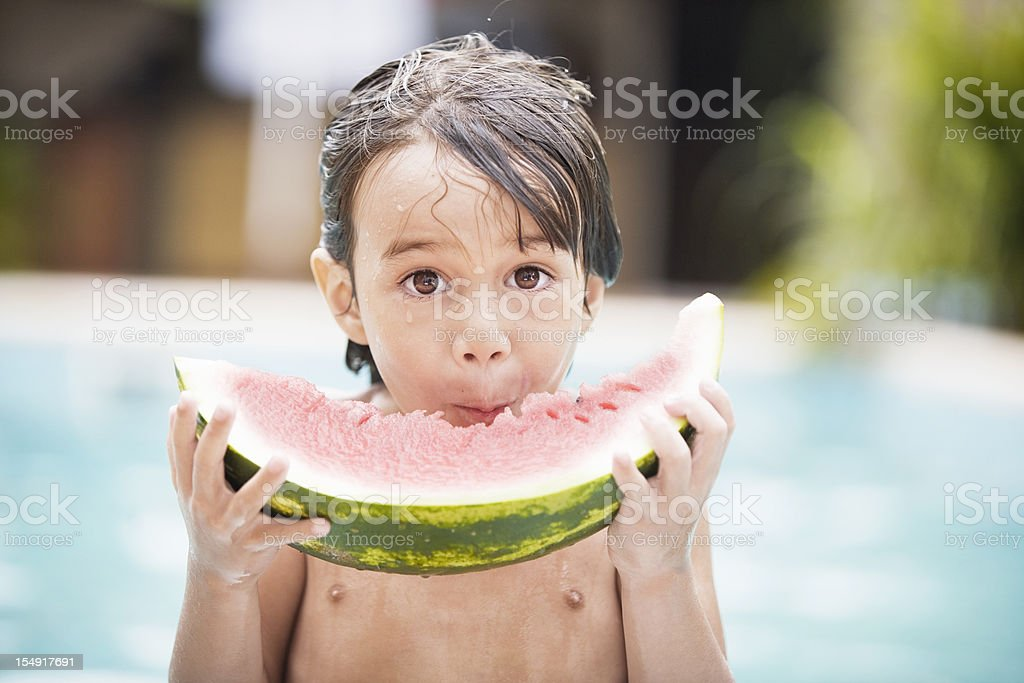 Little Boy Eating Watermelon by Poolside royalty-free stock photo