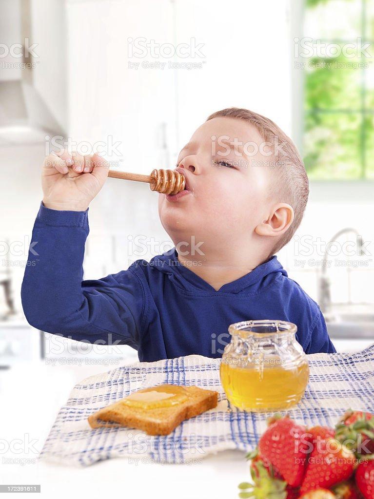 Little boy eats honey royalty-free stock photo